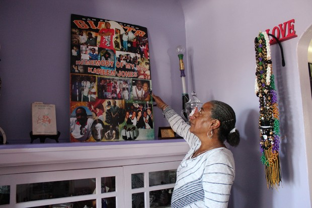NeDina Brocks-Capla stands in her living room in San Francisco. She made a shrine filled with memories of son Kareem Jones, who died of sickle cell anemia in 2013. (Jenny Gold/KHN)