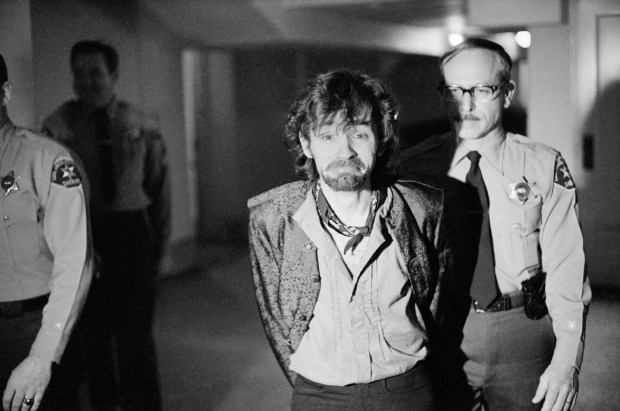 """A scowling Charles Manson goes to lunch after an outbreak in court that resulted in his ejection, along with three women co-defendants, from the Tate murder trial, Dec. 21, 1970. The outburst started after Leslie Van Houten said she wanted to fire her new lawyer, a replacement for missing Ronald Hughes, and hire a woman attorney. Before she was ejected to an adjoining room with the others, Ms. Van Houten slapped a bailiff and told the judge """"I'd strike you if I could."""" (AP Photo/George Brich)"""