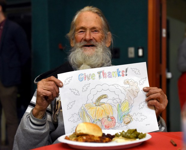 Leo Martin holds up a drawing he colored as he gets a Thanksgiving dinner provided by the San Fernando Valley Rescue Mission, Tuesday, Nov. 22, 2016, at La Iglesia En El Camino in Van Nuys. The Rescue Mission served meals to over 500 people in need at their 17th Annual Thanksgiving Dinner. (Photo by Michael Owen Baker)