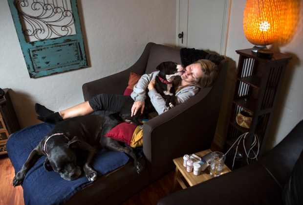 "Trisha Gill, 43, who has daily chronic migraines, spends time with her dogs Gina and Clare, left, at her home in Los Angeles on Tuesday, Nov. 14, 2017. ""I have chronic daily migraines or intractable status migrainous with aura and daily headache, I go blind in one eye to non stop nausea and vertigo. Clare has helped me through seizures by maintaining eye contact with me through the whole thing and then she puts her paw out at the end for me to shake. Seeing the pictures catch the years of disabling pain is sad but I survive despite disability taking so much time to help and aid my coping process,"" said Trisha Gill. (Photo by Ed Crisostomo, Los Angeles Daily News/SCNG)"