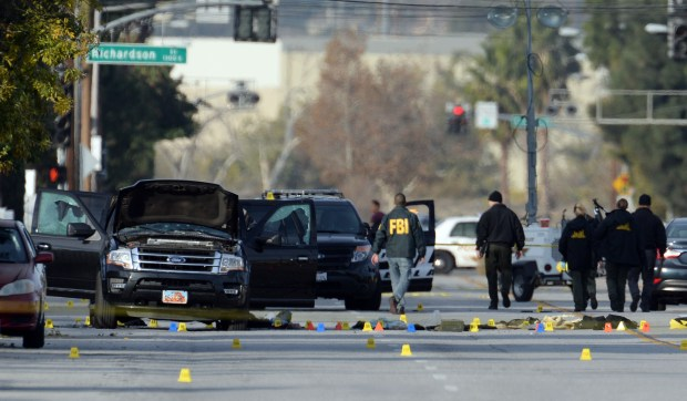 Law enforcement officers investigate the scene on San Bernardino Avenue early Thursday, Dec. 3, 2015, following a police gun battle Wednesday which ended with the killing of the male and female suspects in the mass shooting which killed 14 people at the Inland Regional Center in San Bernardino. (Photo by Will Lester/Inland Valley Daily Bulletin)