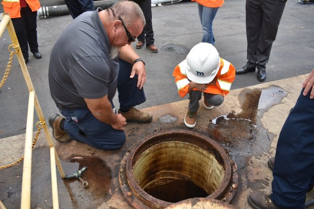 Beck Winters takes a peek into Moulton Niguel Water District's wet well, an underground wastewater collection basin, at the Regional Lift Station where he learns about how the local community's wastewater is collected. (Courtesy of MNWD)