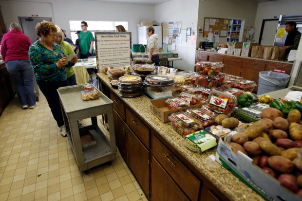 Volunteers Leah Marks and Joi Williams put together a food package at the West Valley Food Pantry located in the Prince of Peace Episcopal Church's kitchen in Woodland Hills. The pantry provides balanced food packages to over 1200 needy clients each month. (Hans Gutknecht/Staff Photographer)