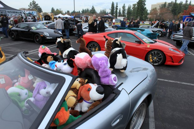 Toys pile up in a Fararri at the Motor4toys charity car show at toy drive held in the parking lot at the Anthem Building in Warner Center. Vistors brought toys in lieu of an entry fee to view exotic and collectable cars. Photo by David Crane/Staff