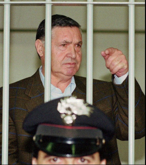 "FILE - In this April 29, 1993 file photo, Mafia ""boss of bosses"" Salvatore ""Toto"" Riina, is seen behind bars, during a trial in Rome. Italy's justice minister has given special permission for family bedside visits to the comatose top Mafia boss. Italian media reports Riina died early Friday, Nov. 17, 2017. (AP Photo/Giulio Broglio)"