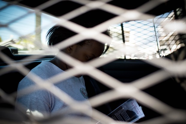A suicidal teen sits in the back of a Los Angeles County Sheriff's Mental Evaluation Team vehicle outside Anderson Elementary School in Compton as MET finds a mental health facility that can take her for a 72-hour psychiatric hold. The school gave her a lunch and book. (Photo by Sarah Reingewirtz, Los Angeles Daily News/SCNG) .