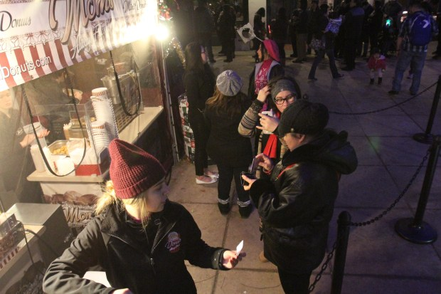 A group stands in line to buy mini doughnuts during the Festival of Lights in Riverside Saturday, Dec. 26, 2015. (File Photo)