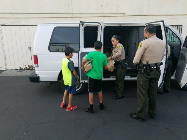 Deputies from the Los Angeles County Sheriff's Department's La Puente Special Assignment team, aided by local charity organizations, surprised more than 200 local families with free Thanksgiving food boxes this week. (Courtesy, Los Angeles County Sheriff's Department)