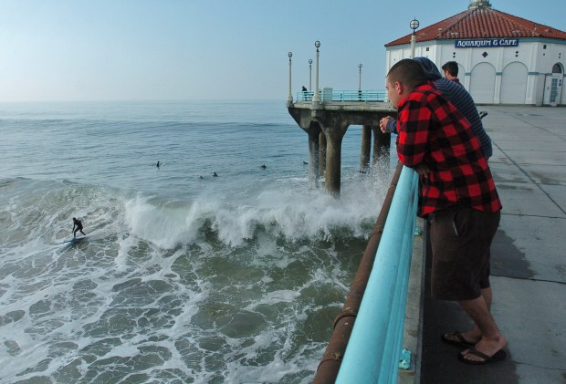 Heavy surf pounds South Bay West facing beaches. Visitors to the Manhattan beach pier watch surfers ride waves. File Photo