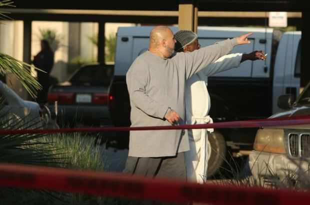 Residents watch the activity outside the Village Drive Apartments where two women and a man were killed, and another man was critically wounded early Wednesday, Jan. 4, 2017, in Fontana. A man is in custody, officials said.(Stan Lim, The Press-Enterprise/SCNG)