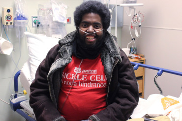 Marqus Valentine sits on the edge of his hospital bed, following a blood transfusion at Edward Hospital in Naperville, Ill. (Jenny Gold/Kaiser Health News)