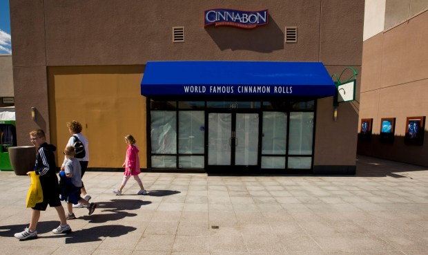 A family walks by the closed Cinnabon store, with paper over the windows, at Anaheim's GardenWalk in 2010. The struggling mall is again for sale. /File photo by Mark Rightmire, The Orange County Register/SCNG