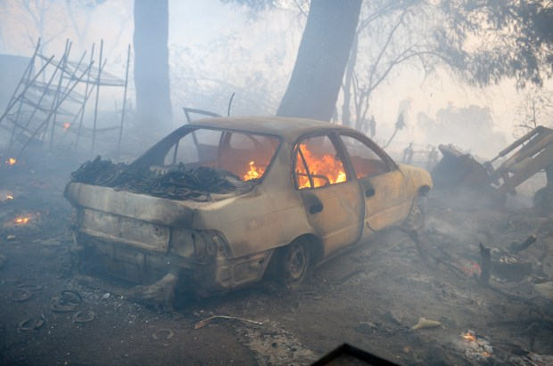 A car continues to burn after the Creek fire roared through the 11500 block of Cassara Avenue in Lake View Terrace Tuesday morning. (Photo by David Crane, Los Angeles Daily News/SCNG)