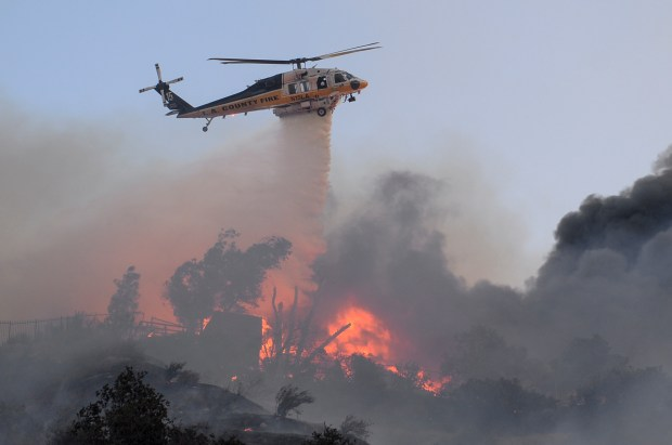 An L.A. County helicopter makes a water drop on a fully involved home on Hillrose street in Sunland during the Creek fire on Tuesday, Dec. 5. (Photo by David Crane, Los Angeles Daily News/SCNG)