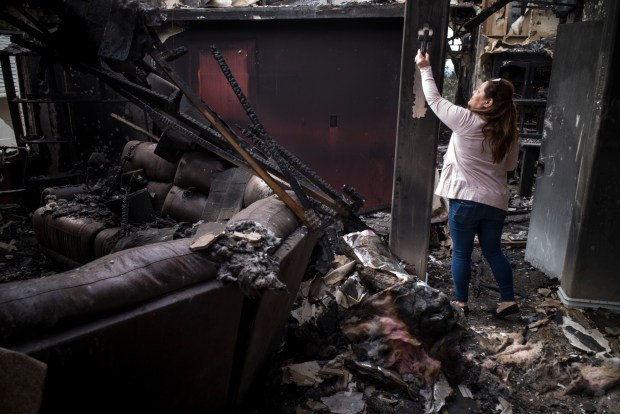 Maria Hernandez retrieves a cross from her destroyed home on Gavina Avenue in Sylmar Sunday, December 10, 2017. Hernandez's home was burned in the Creek fire which roared through the Sylmar neighborhood early Tuesday morning. On Sunday she and her husband returned to see what remained of their home of 14 years. (Photo by David Crane, Staff Photographer/SCNG)