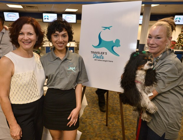 """(l-r) Cate Roman, a professor at Woodbury University and one of her students, Samm Deboda, stand with Candy Malatesta and her comfort dog named, Miss Sherman Oaks. Deboda designed the logo, and came up with the name """"Traveler's Tails"""" that appears on the vests worn by the comfort animals. Hollywood Burbank Airport unveiled its new logo and name on the façade of the terminal tower. The event was attended by Burbank-Glendale-Pasadena Airport Authority officials as well as City Council Members from Burbank. After the unveiling the Airport introduced its new pet therapy program, Traveler's Tails, providing stress relief and comfort for passengers through interaction with certified therapy dogs. Burbank, CA 12/14/2017 (Photo by John McCoy, Los Angeles Daily News/SCNG)"""