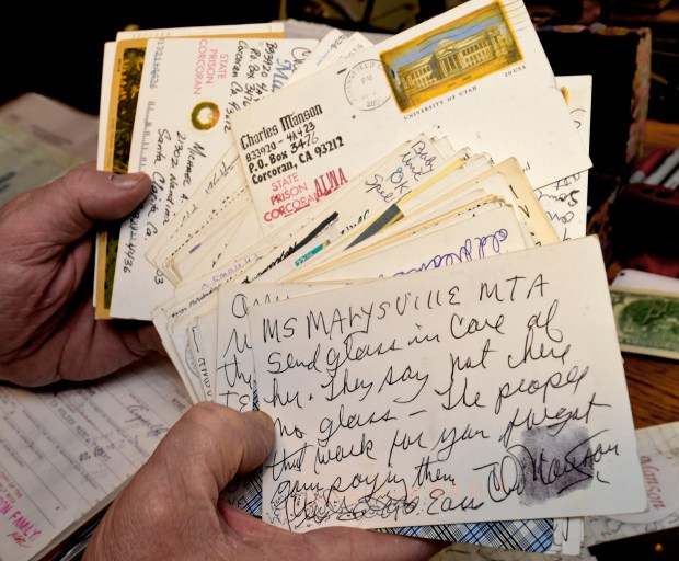 Michael Channels shuffles through some of the 150 post cards he received from Charles Manson over the many years of their correspondence. (Photo by Dan Watson / SCNG December 12, 2017)