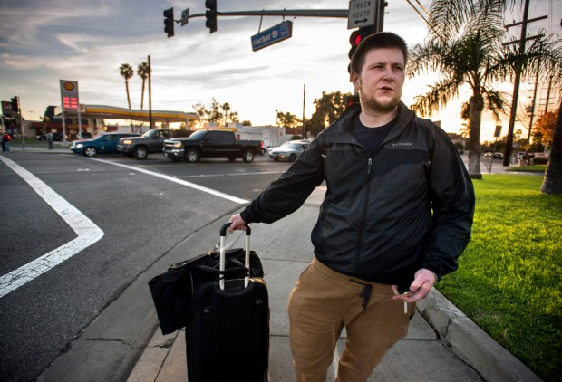 Blake Lowe, 24, of Seattle drags his suitcase down Harbor Blvd. in Costa Mesa as he makes his way to a detox center for heroin addiction, yet again. (Photo by Mindy Schauer, Orange County Register/SCNG)
