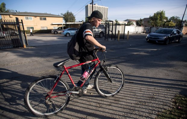 Sergius Harty, 25, habitually scans the ground for cigarette butts, change or anything else useful to him, as he gets ready to shoot heroin in Costa Mesa.(Photo by Mindy Schauer, Orange County Register/SCNG)