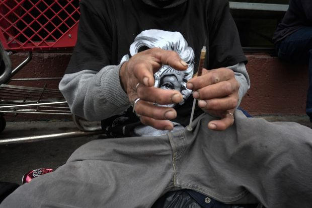 A drug addict prepares a needle to inject himself with heroin in front of a church in the Skid Row area of Los Angeles. I(AP Photo/Jae C. Hong)