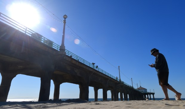 Under clear blue skies and temperatures in the low 60's, a man walks along the beach next to the Manhattan Beach pier on Thursday, December 21, 2017. (Photo by Scott Varley, Daily Breeze)