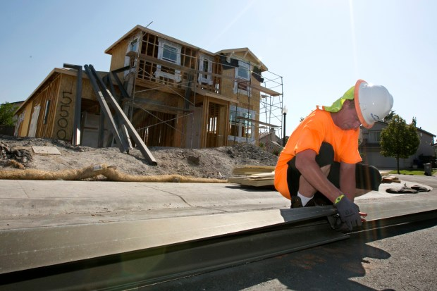 In this photo taken Wednesday, Aug. 16, 2017, sheet metal worker Benjamin Voget prepares to install a gutter on a home under construction in Sacramento, Calif. Gov. Jerry Brown and Democratic legislative leaders promised to tackle California's housing crisis in the final weeks of the legislative session by pushing a package that includes money for low-income housing and regulatory reforms. Lawmakers say the housing shortage is affecting people throughout the state at nearly all income levels. (AP Photo/Rich Pedroncelli)