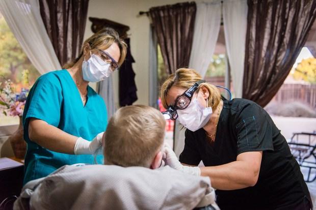 Dental hygienist Gita Aminloo (right) and assistant Shirin Tavakolinia clean a patient's teeth. (Heidi de Marco/California Healthline)