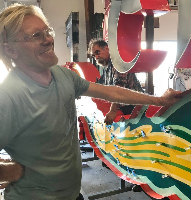 Richard Ankrom, left, jokes that his claim to fame is the long-ago stunt in which he fixed a Caltrans sign. He's seen here in November in Pomona with Paul Greenstein, repairing a Grauman's Chinese Theatre neon dragon. (Photo by David Allen)