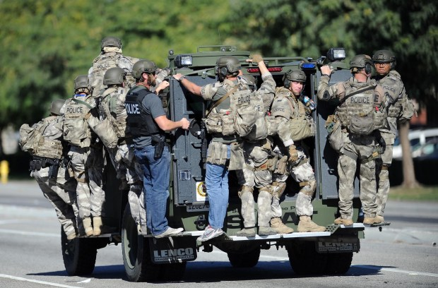 A SWAT vehicle carries police officers, from multiple agencies, north on Waterman Avenue, in San Bernardino after two shooters killed 14 people and injured 22 others at the Inland Regional Center on Wednesday, December 2, 2015. The two shooters, Syed Farook, 28, and his wife Tashfeen Malik, 29, of Redlands, were killed hours later in a gun battle with authorities. (Staff file photo, The Sun/SCNG)