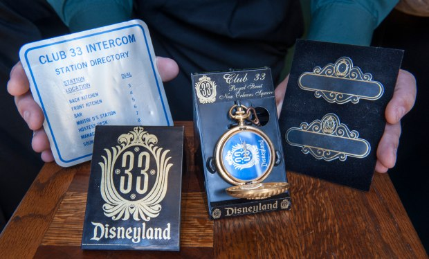 Vintage souvenirs of Disneyland's exclusive private Club 33, owned by Kevin Doherty include a 1967 placard from the bar, from left, a 1985 prototype for a pocket watch, and cast member name tags. (Photo by Mindy Schauer, Orange County Register/SCNG)