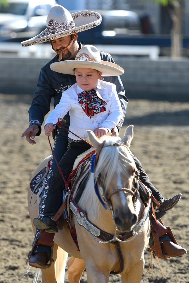 Emiliano Martinez,6, takes the reins from Joaquin Raigosa who rides for the Hermanos Banuelos Charro Team. The pair were warming up before Raigosa performed in Equestfest, held at the Los Angeles Equestrian Center. The event showcased many of the equestrian units that will participate in the Rose Parade on New Year's Day. Burbank, CA 12/29/2017 (Photo by John McCoy, Los Angeles Daily News/SCNG)