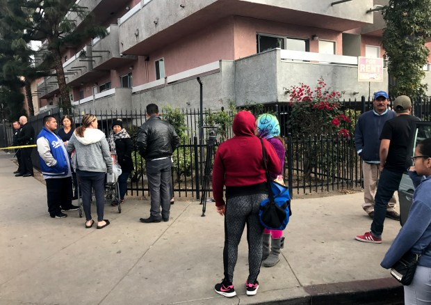 People wait to go back to their apartments on Wednesday morning, Dec. 20, 2017, in the 8900 block of Orion Avenue in North Hills. An officer-involved shooting occurred after 1 a.m. Wednesday in the area and authorities were investigating. (Photo by Wes Woods II)