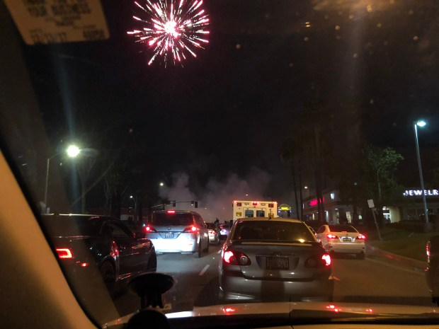 This photo, taken by a driver in Fullerton, shows fireworks and smoke from a car during a massive meetup of car enthusiasts. (Courtesy photo)