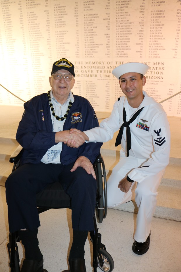 Navy Petty Officer Second Class Christopher B. Camire, right, of Norco, greets Fire Controlman 3rd Class Lauren Bruner, 97, at a ceremony at the USS Arizona Pearl Harbor memorial on Dec. 5, 2017. Bruner was the second to last person to leave the ship before it sank.