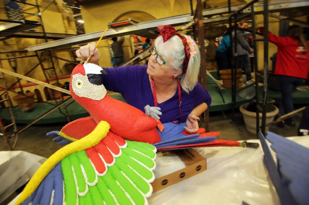 Kelly Nassiri, of Simi Valley, glues crushed rice onto a Macaw that will decorate Riverside's first entry in the Rose Parade since the 1950's, the Mission Inn 25th Annual Festival of Lights, at Fiesta Parade Floats in Irwindale, CA., Tuesday, December 26, 2017. Riverside's 2018 float celebrates 25 years of the Mission Inn Hotel and Spa putting on the annual Festival of lights. The float also is designed to thank Duane and Kelly Roberts the Keepers of the Inn, who have invested so much in the historic hotel. (Photo by James Carbone for the Riverside Press Enterprise)