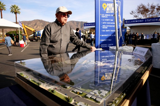 Gerald Collier, 81, of Claremont, who says he opposes extension of the Foothill Gold Line any further than Pomona, stands next to a diorama of what will be the Pomona station during a groundbreaking ceremony for the extension of the Foothill Gold Line at Citrus College in Glendora, Calif. on Saturday, Dec. 2, 2017. (Correspondent photo by Trevor Stamp)