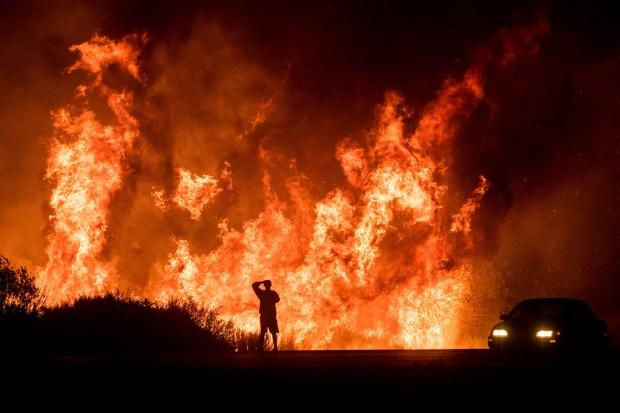 A motorists on Highway 101 watches flames from the Thomas fire leap above the roadway north of Ventura, Calif., on Wednesday, Dec. 6, 2017. As many as five fires have closed highways, schools and museums, shut down production of TV series and cast a hazardous haze over the region. About 200,000 people were under evacuation orders. No deaths and only a few injuries were reported. (AP Photo/Noah Berger) Noah Berger