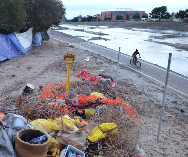 After recent rains the Santa Ana River is starting to be filled with water.  A man rides along the bike trail through the homeless encampment across from Honda Center. (Photo by Bill Alkofer, Orange County Register/SCNG)