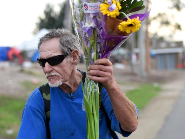 """Patrick Hogan produces a handwritten newsletter that he calls """"Riverbed Wash."""" He hand delivers it from his bicycle to other homeless people. He often returns from Mary's Kitchen with some flowers for one of his friends. Mary's Kitchen serves meals to homeless people. (Photo by Bill Alkofer, Orange County Register/SCNG)"""