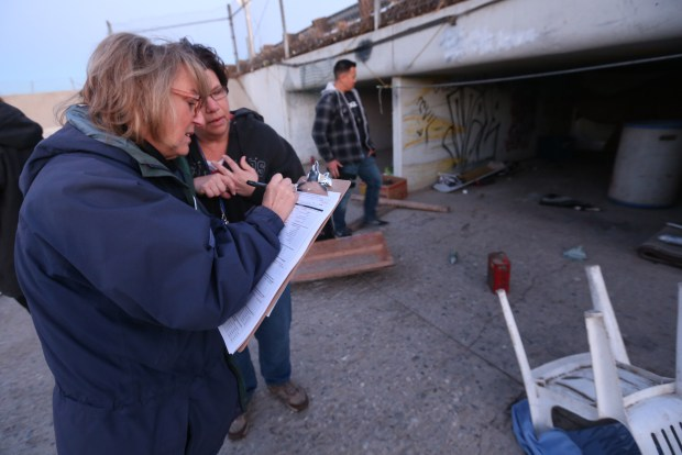 Luisa Tassan, a volunteer from Riverside, left, and Jill Kowalski, with the Riverside County Department of Public Social Services Homeless Program Unit, fill out a survey after interviewing homeless people living in a flood control channel under Van Buren Blvd. during the annual Point-In-Time Homeless Count and survey in Jurupa Valley on Tuesday, Jan. 23, 2018. (Stan Lim, The Press-Enterprise/SCNG)