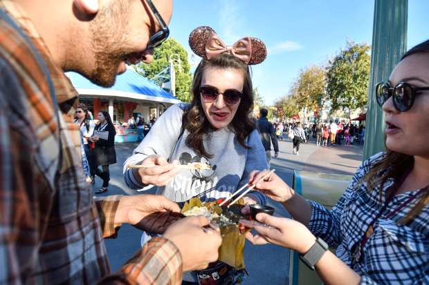 Isaacs Simms, left, Sarah Pollock center, and Brenda Rogers sample the Banh ChuÕng (sticky rice cake with pork) during the first day of Disney's Lunar New Year celebration at California Adventure in Anaheim on Friday, Jan 26, 2018. (Photo by Jeff Gritchen, Orange County Register/SCNG)