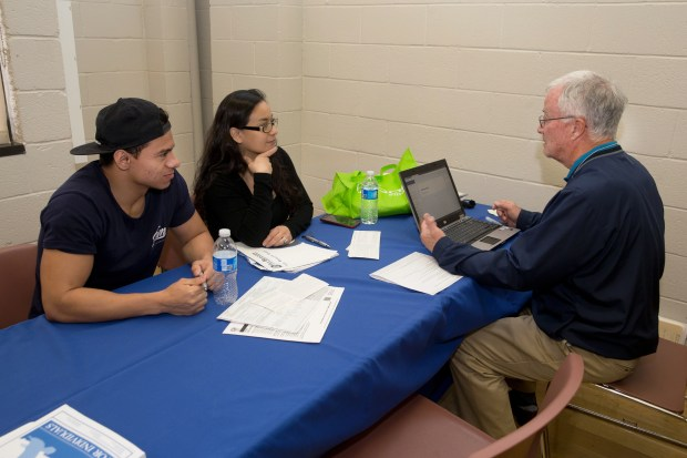 At an Anaheim free tax preparation fair, Patricia Lara and her son, Joseph Ducret, get help with their returns from IRS-trained volunteer Stan Manley (Photo by David Kawashima/ Orange County United Way)
