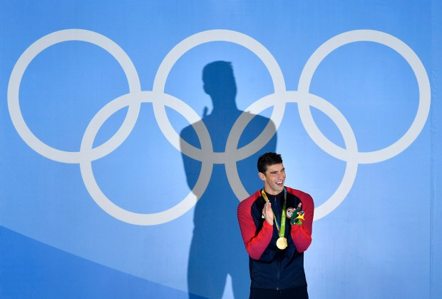 United States' Michael Phelps laughs after he was awarded the gold medal during the medal ceremony for the men's 200-meter butterfly final during the swimming competitions at the 2016 Summer Olympics, Tuesday, Aug. 9, 2016, in Rio de Janeiro, Brazil. (AP Photo/Martin Meissner)