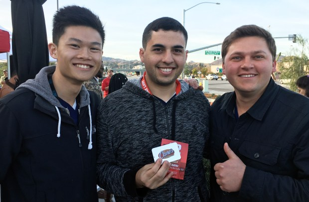 "Rodrigo Robles, center, celebrates winning ""Cane's for a year"" with friends Brian Choi and Samuel Karavan."