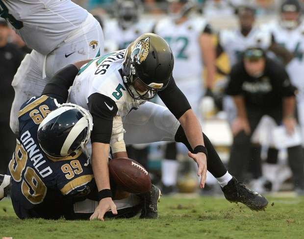 In this Oct. 15, 2017, file photo, Jacksonville Jaguars quarterback Blake Bortles (5) loses the ball as he is sacked by Los Angeles Rams defensive tackle Aaron Donald (99) during the second half of an NFL game, in Jacksonville, Fla. (AP Photo/Phelan M. Ebenhack, File)