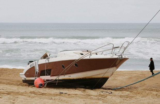 The speedboat belonging to sportswear maker Quiksilver CEO Pierre Agnes lays ashore on the beach of Hossegor, southwestern France, Tuesday, Jan. 30 2018. Authorities have sent boats and helicopters off the coast of southwest France to search for Pierre Agnes, after his empty boat was found washed ashore. (AP Photo)