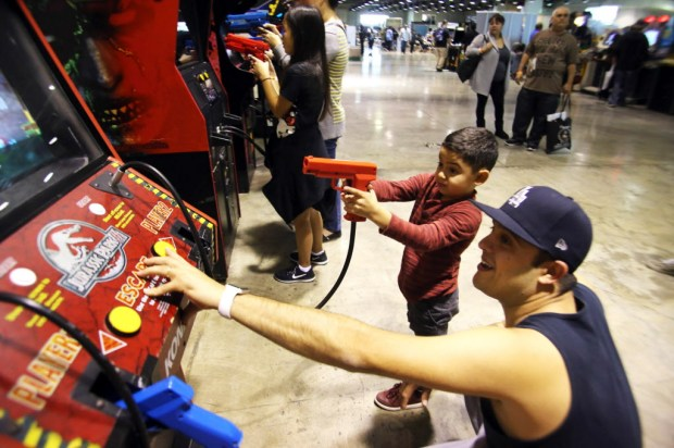 Thomas Servantes of Murrieta, with his son Thomas Jr., 6, play the Jurassic Park video game during Retro City Festival, with over 200 arcade games, consoles, and pinball machines, at the Pomona Fairplex in Pomona, CA., Saturday, January 20, 2018. (Photo by James Carbone for the Inland Valley Daily Bulletin)