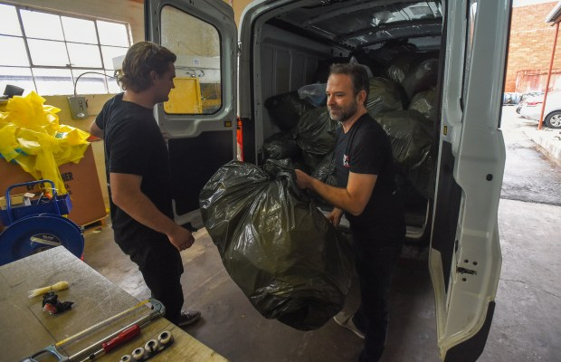 Ryan Olliges, left, and Jaysen Harris unload a fresh haul of recycled carbon fiber scraps at their company 121c in Gardena on Monday, Jan 8, 2018. Using the scrap trimmings they gather from aerospace corporations, their company can make a variety of carbon fiber products, such as skateboard decks. (Photo by Scott Varley, Daily Breeze/SCNG)