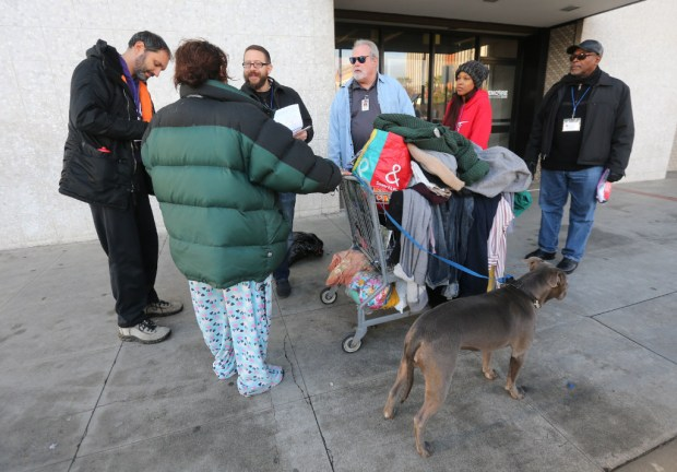 A homeless women with her dog is met with a group of volunteers and interviewed during an annual homeless count on Tuesday, Jan. 24, 2017 in Riverside. (Stan Lim, The Press-Enterprise/SCNG)