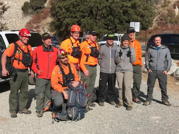 Rescued hiker Bethany Sloan, 32, of Redlands gives a thumbs up after she was hoisted from the top of Big Falls by a San Bernardino County Sheriff's Department helicopter Sunday, Jan. 7, 2018. She stands with seven San Gorgonio Search and Rescue team members who hiked all night trying to find her and a team member who helped staff the command post overnight.
